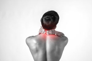 Muscular man use handles at the neck to relieve pain isolated on